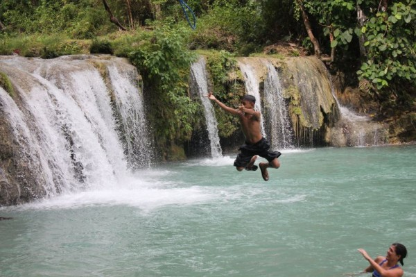 Junior doing the spider-man pose at Cambugahay Falls (Tia watching) (Siquijor)