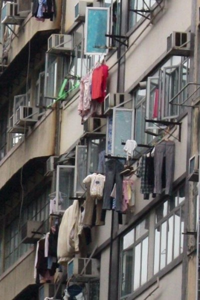 The people in Hong Kong hang dry their clothes right outside their apartment window