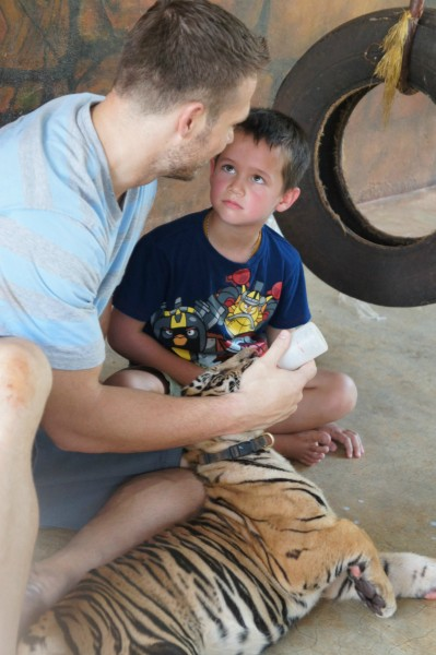 Mason learning from his father how to feed a tiger cub.