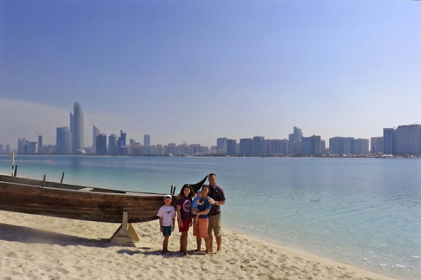 Family photo with the Abu Dhabi skyline.