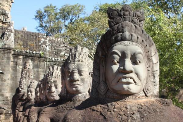 Stone warrior on a bridge leading into the 12th century city of Angkor Thom.