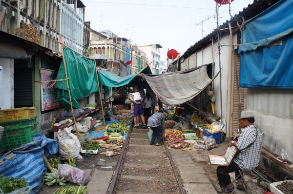 Train Umbrella Market...A train comes through here twice a day and the vendors move their items back while it passes