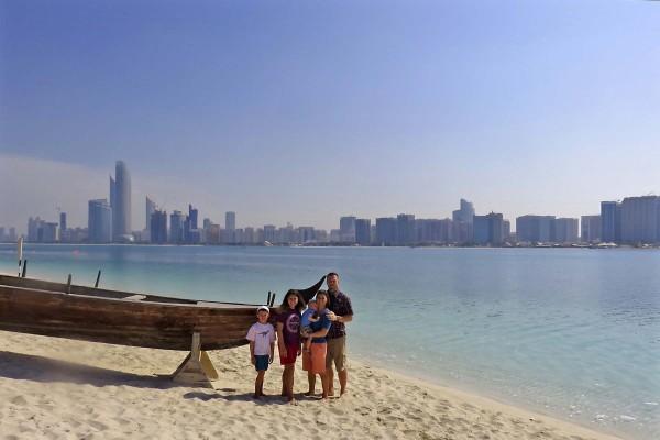 Family photo with the Abu Dhabi skyline.